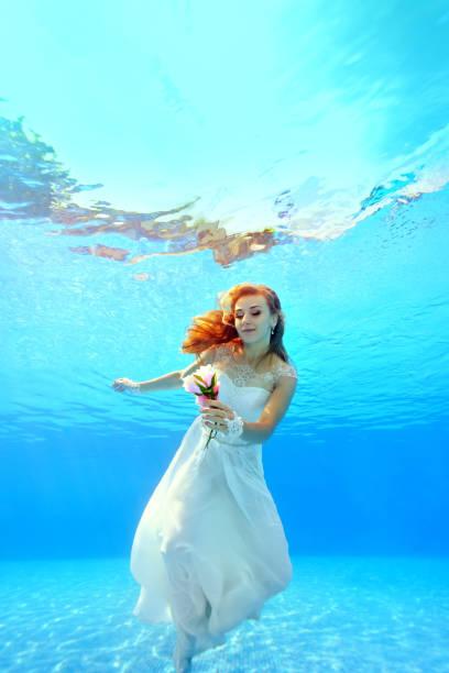 schöne braut in einem weißen kleid schwimmt unter wasser mit einer blume in der hand. lächelt und schaut die blume. porträt. vertikale ausrichtung. ein blick unter wasser - meerjungfrau kleid stock-fotos und bilder