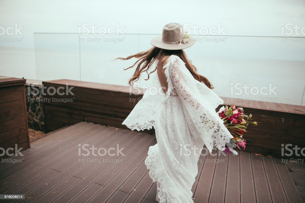 beautiful bride in bohemian wedding dress and hat with bouquet стоковое фото