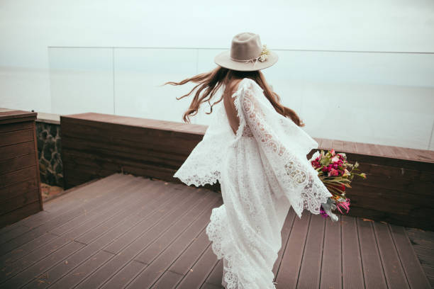 beautiful bride in bohemian wedding dress and hat with bouquet - wedding fashion stock pictures, royalty-free photos & images