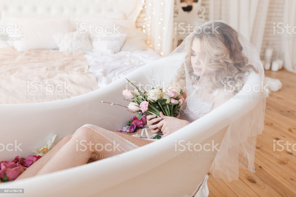 1317a16bb88 Beautiful bride in lingerie lies in a bath with a bouquet of flowers  covered with veil. Bedroom interior - Stock image .