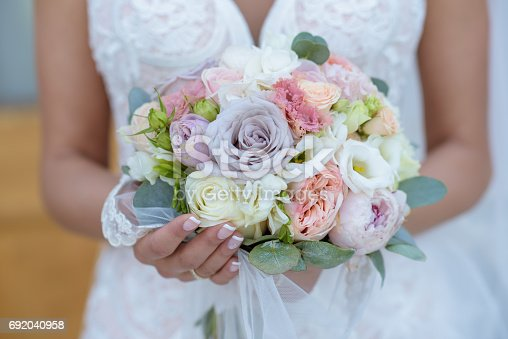 istock Beautiful bride is holding a wedding colorful bouquet 692040958