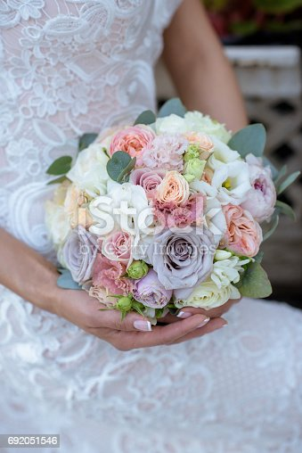 istock Beautiful bride is holding a wedding colorful bouquet 692051546