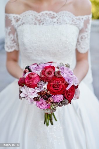 istock Beautiful bride is holding a wedding colorful bouquet 695271014
