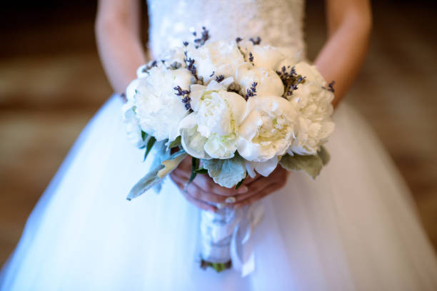 Beautiful bride is holding a wedding colorful bouquet stock photo