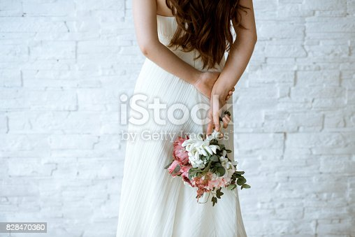 istock Beautiful bride is holding a wedding colorful bouquet 828470360