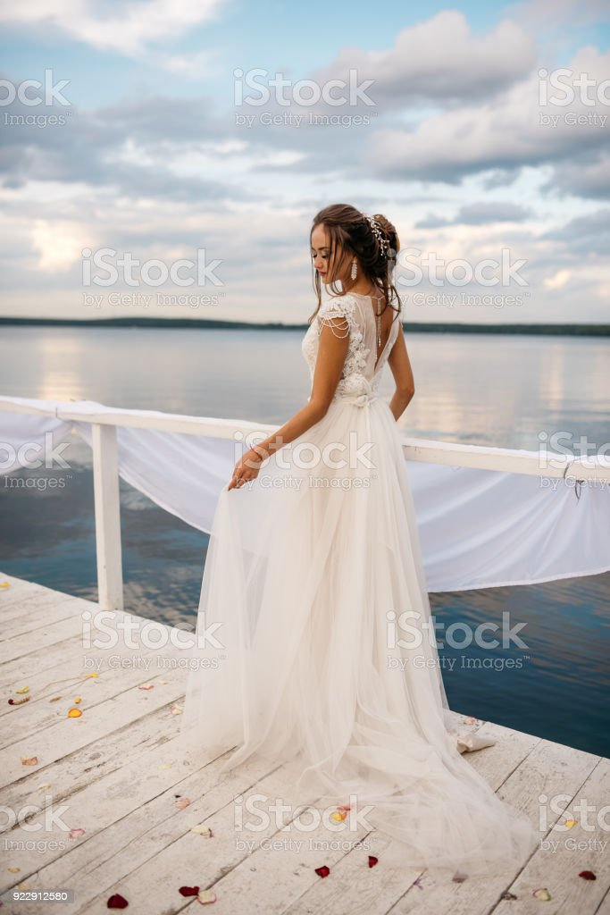 A beautiful bride is standing on the pier. Lake and cloudy sky on the background stock photo