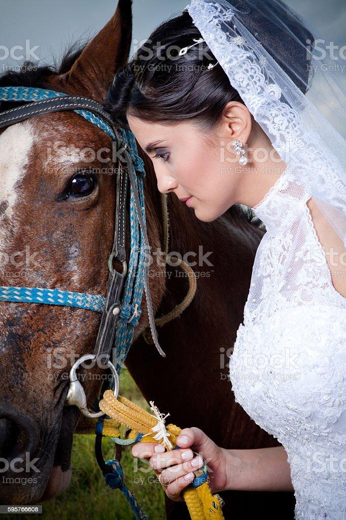 Beautiful Bride Looking at Horse in Farm - foto de acervo