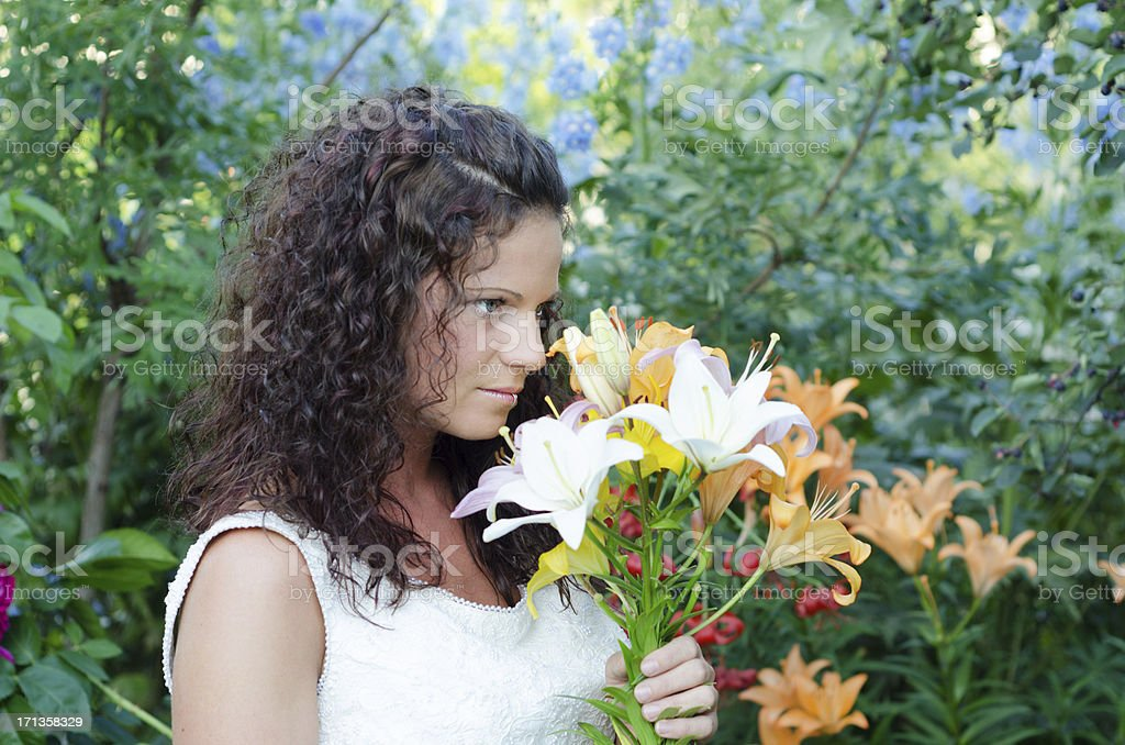 Beautiful bride looking over bouquet royalty-free stock photo