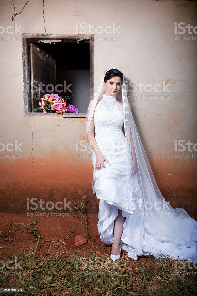 Beautiful Bride Outside Old Farm House Window and Bouquet - foto de acervo