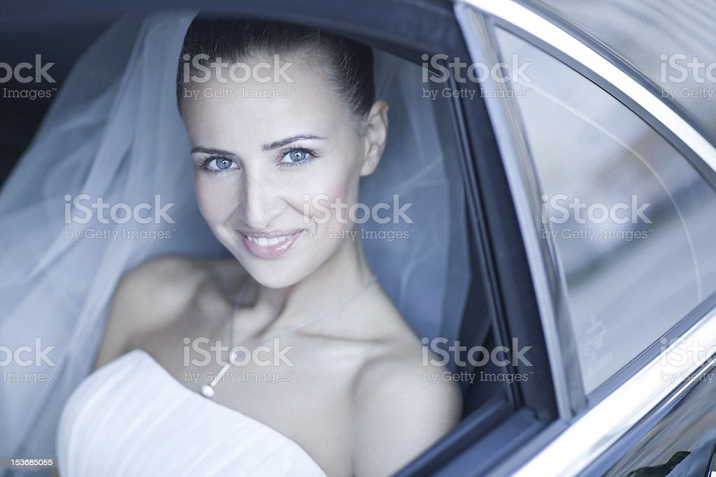 Beautiful bride pictured inside a car before her wedding stock photo