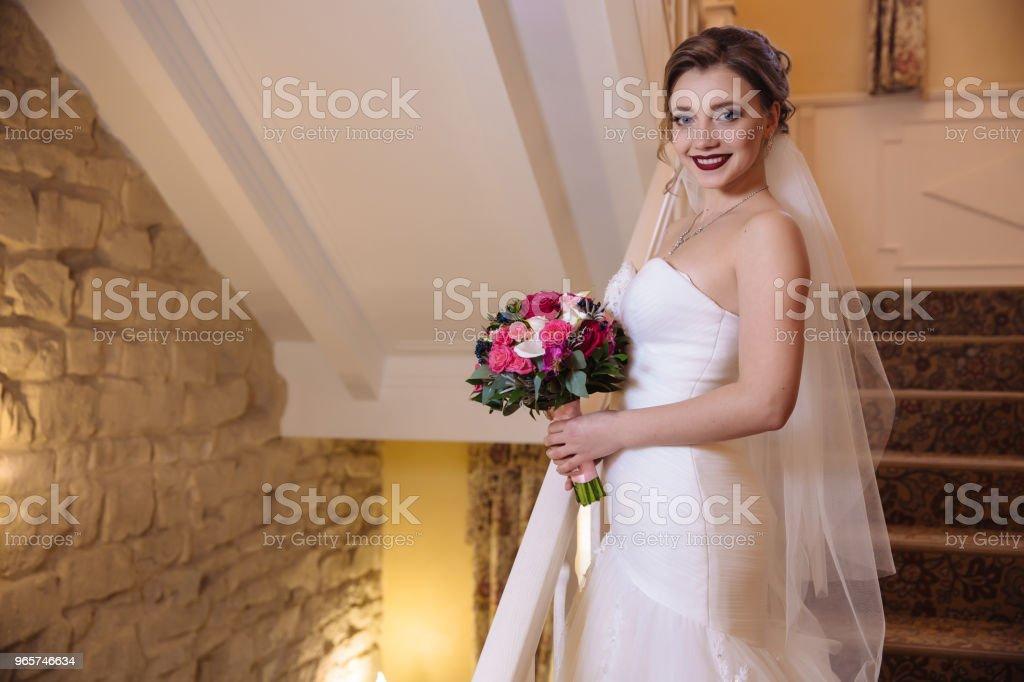 Mooie bruid poseren met een boeket bloemen glimlachend en staande op de trap. De verplichte trouwjurk benadrukt het figuur van het meisje - Royalty-free Binnenopname Stockfoto