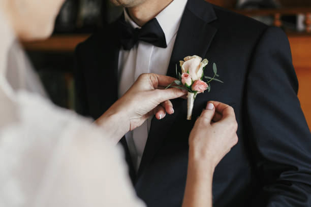 Beautiful bride putting on stylish simple boutonniere with roses on picture id1003459290?b=1&k=6&m=1003459290&s=612x612&w=0&h=d0xmnli9joedjorbqttberkmvlatcamt3wxqbyajw8w=