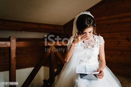 istock Beautiful bride reading letter from the groom for love. Bride's tears of happiness, joy. The bride sits at window and reads letter to groom. Wedding vows. Morning of the bride. Dress with lace. 1131788369