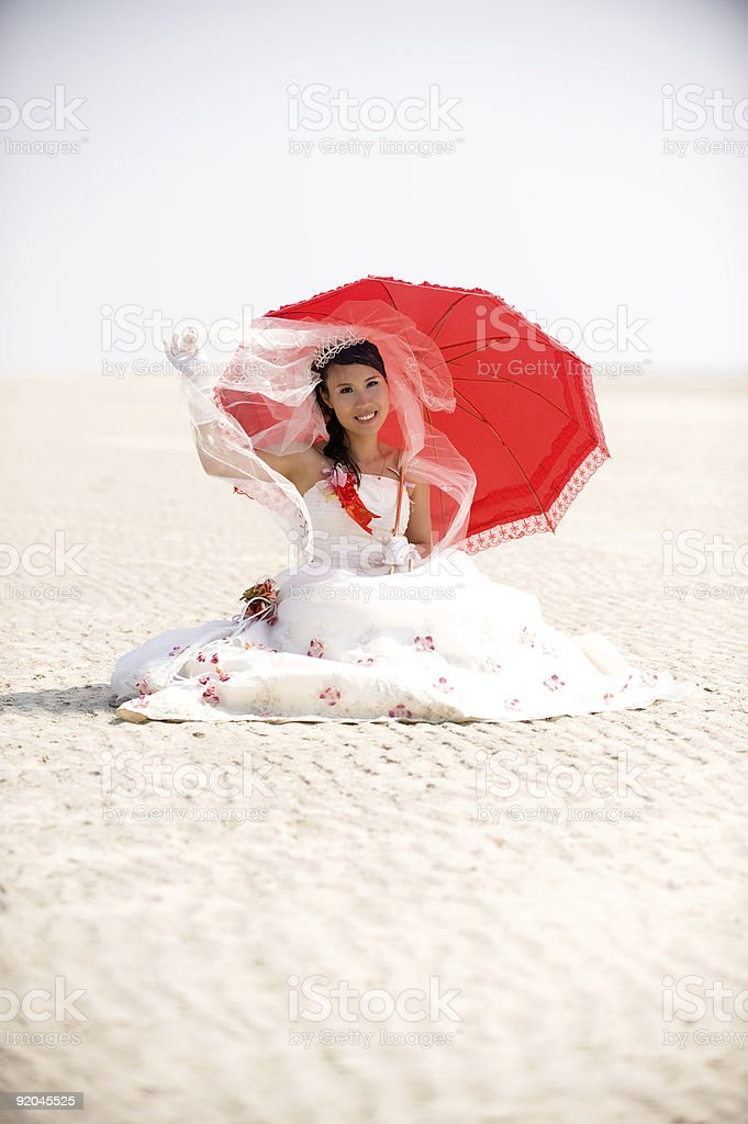 Beautiful Bride Sitting in Sand royalty-free stock photo
