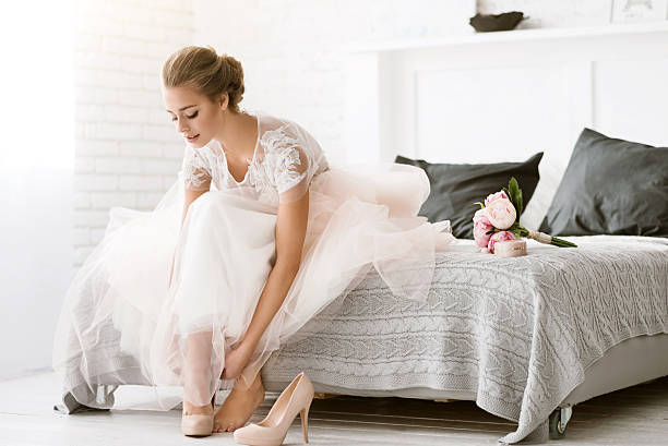 Beautiful bride sitting in the white colored room stock photo