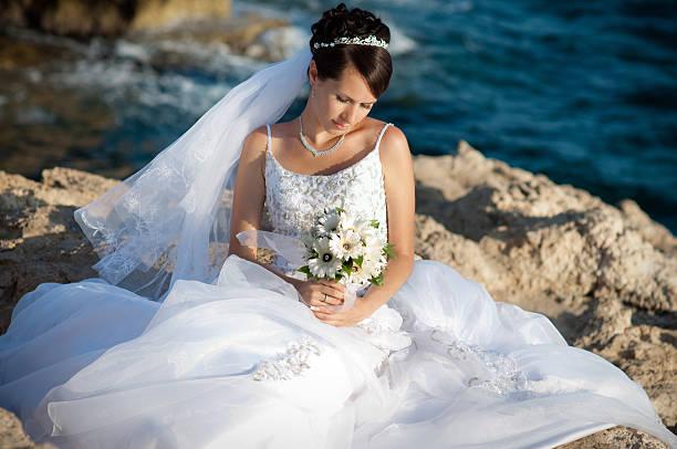 Beautiful bride sitting near the sea stock photo