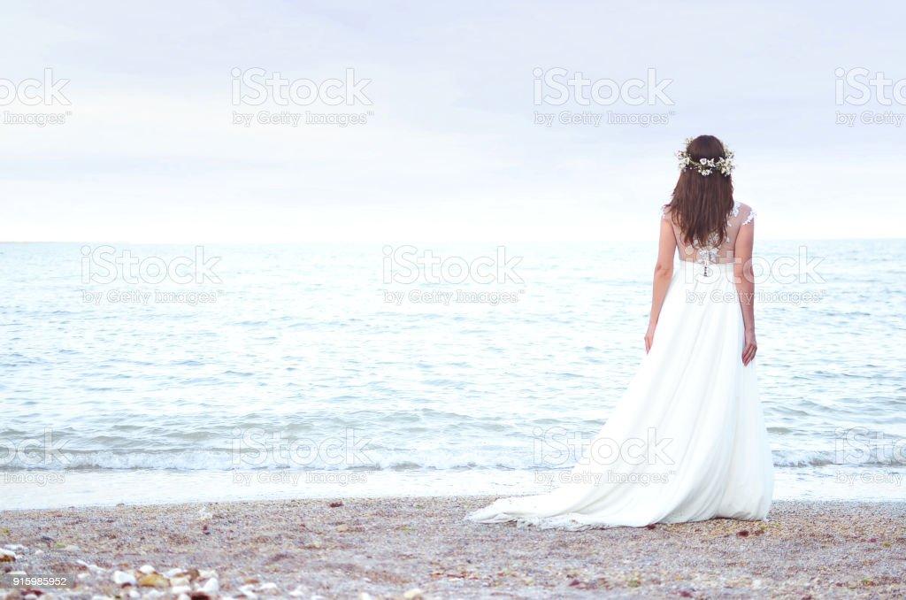 Schöne Braut steht über dem Meer. Braut zu Fuß am Strand – Foto