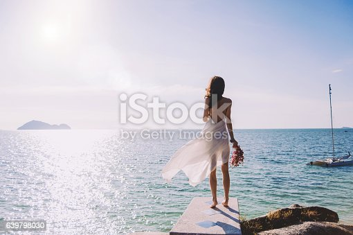 istock beautiful bride stands on a cliff above the sea 639798030