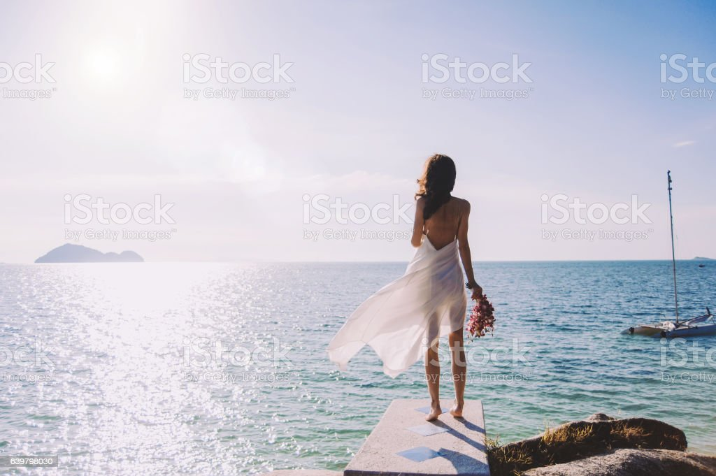 beautiful bride stands on a cliff above the sea - foto de acervo