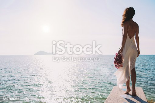 istock beautiful bride stands on a cliff above the sea 639798054