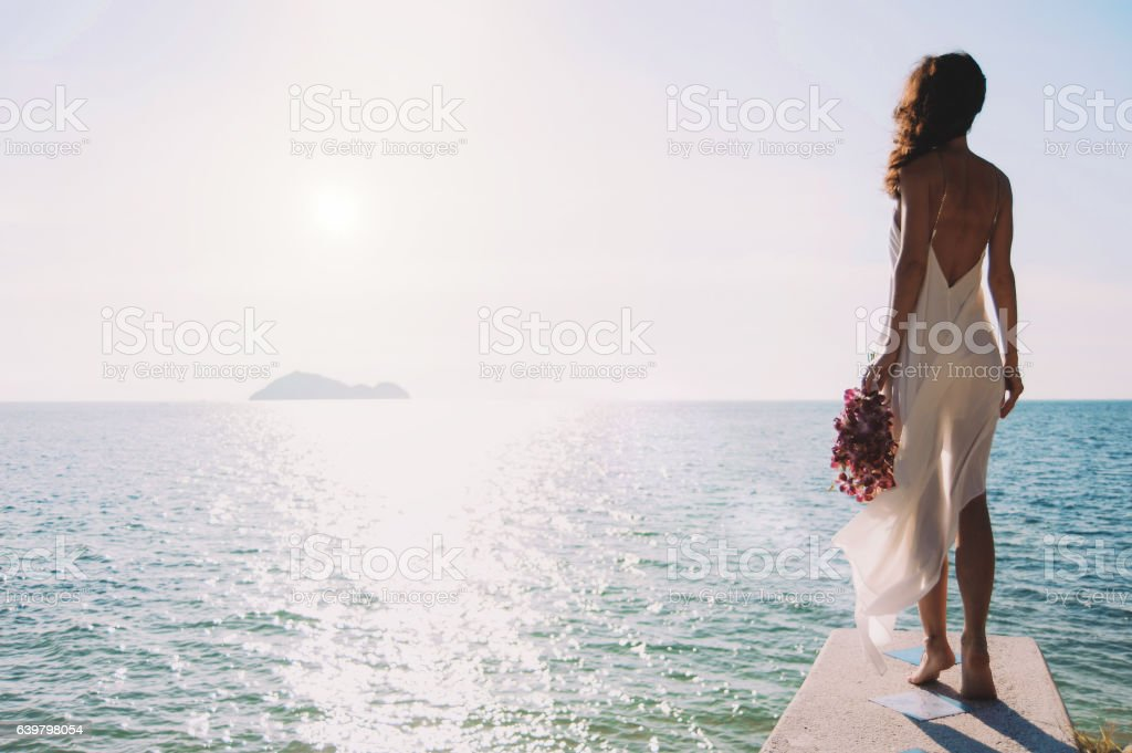 beautiful bride stands on a cliff above the sea stock photo