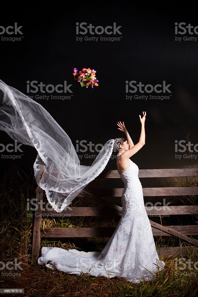 Beautiful Bride Throwing Bouquet outdoors at night - foto de acervo