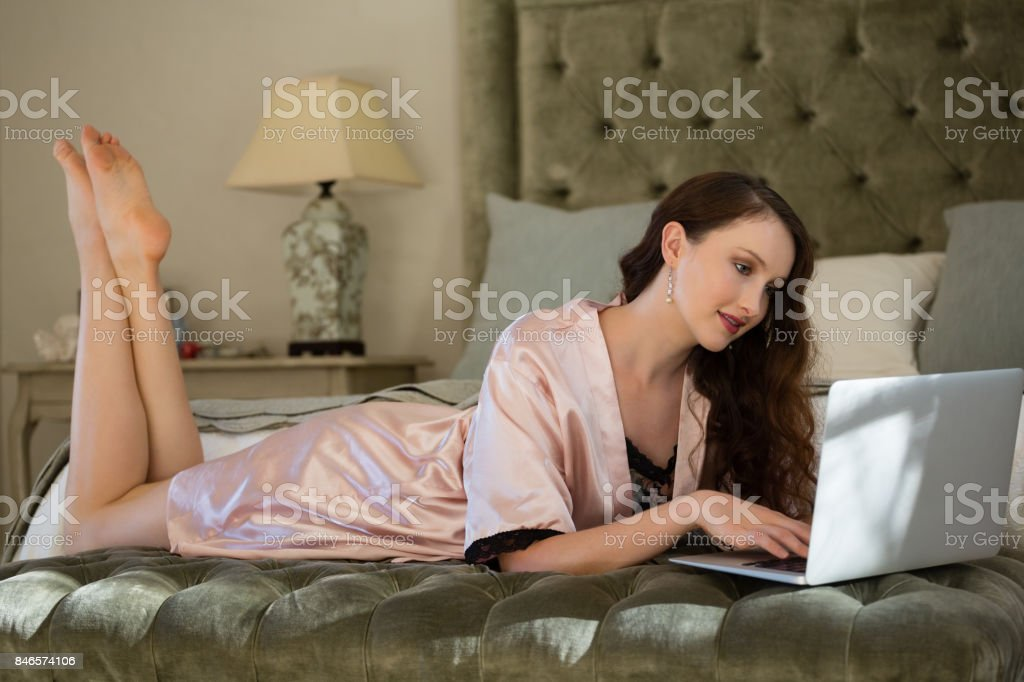 Beautiful bride using laptop while relaxing on bed stock photo