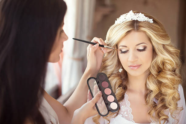 Beautiful bride wedding with makeup and curly hairstyle. Stylist Beautiful bride wedding with makeup and curly hairstyle. Stylist makes make-up bride on wedding day. Beauty portrait of young woman at morning. stage make up stock pictures, royalty-free photos & images
