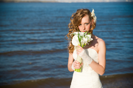 674214372 istock photo Beautiful bride with a bouquet on coast of river 488913753