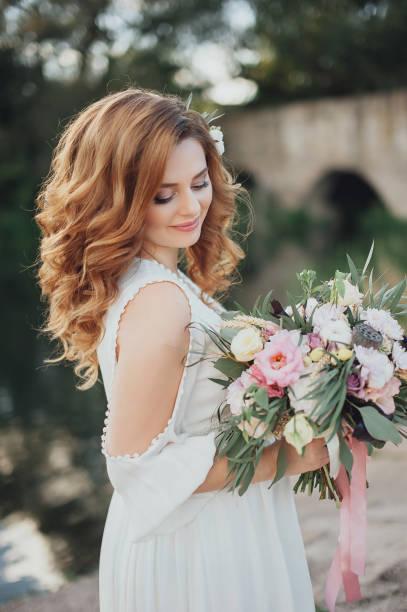 beautiful bride with a stylish bouquet of different flowers. rustic - hochzeitsfrisur boho stock-fotos und bilder