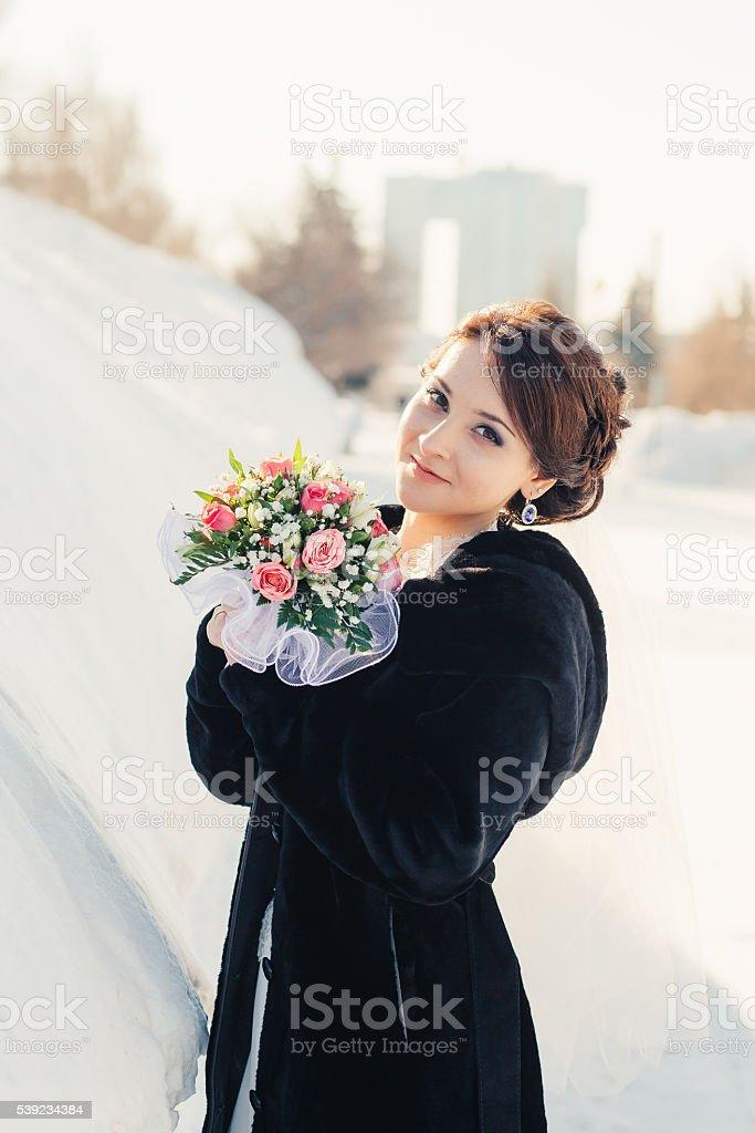 Hermosa novia con ramo posando al aire libre en la nieve foto de stock libre de derechos