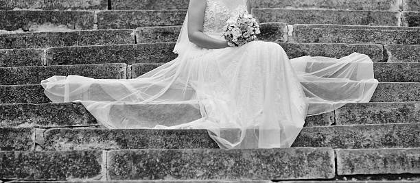 Beautiful bride with bouquet sitting on stairs. stock photo