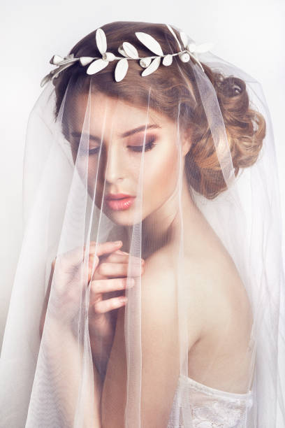 beautiful bride with fashion wedding hairstyle - on white background. close-up portrait of young gorgeous bride. wedding. beautiful bride portrait with veil over her face - veil stock pictures, royalty-free photos & images