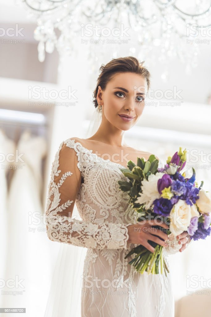 Beautiful bride with floral bouquet in wedding atelier stock photo