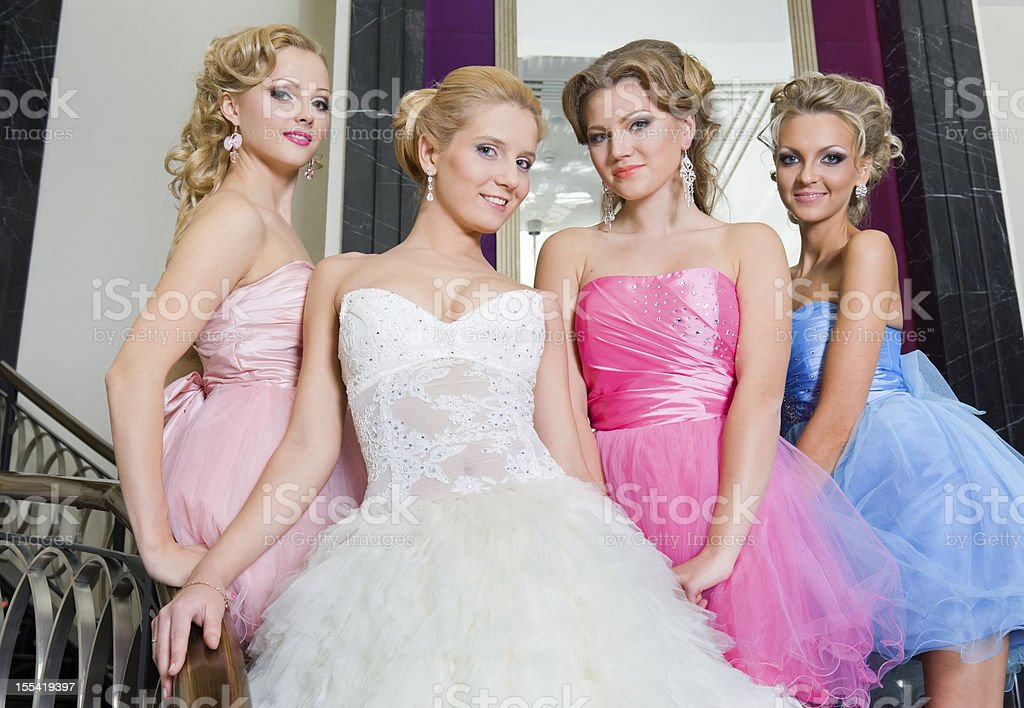 Beautiful bride with her bridesmaids on the stairs stock photo