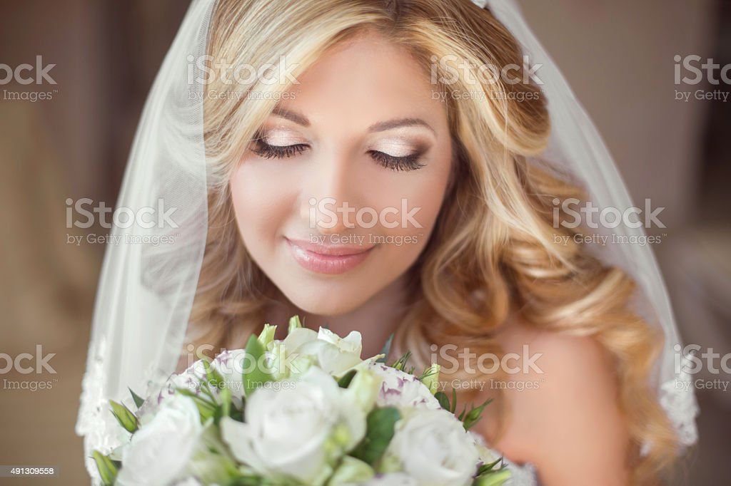 Beautiful bride with wedding bouquet of flowers. Makeup. Blond stock photo