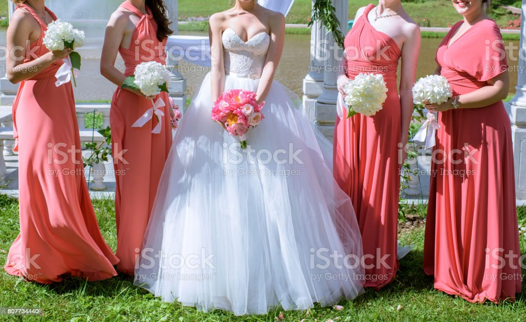 Beautiful bridesmaids and bride in bridal gown with bouquets in the nature stock photo
