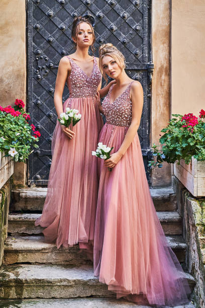 Beautiful bridesmaids in gorgeous elegant stylish red pink violet floor length v neck chiffon gown dress decorated with sequins sparkles and rhinestones holding flowers bouquets. Wedding day in old beautiful European city. stock photo