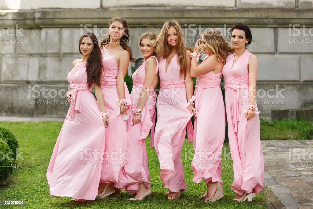 Beautiful bridesmaids in pink dresses posing and looking to camera at wedding day. Group wedding portrait of guests without bride and groom stock photo