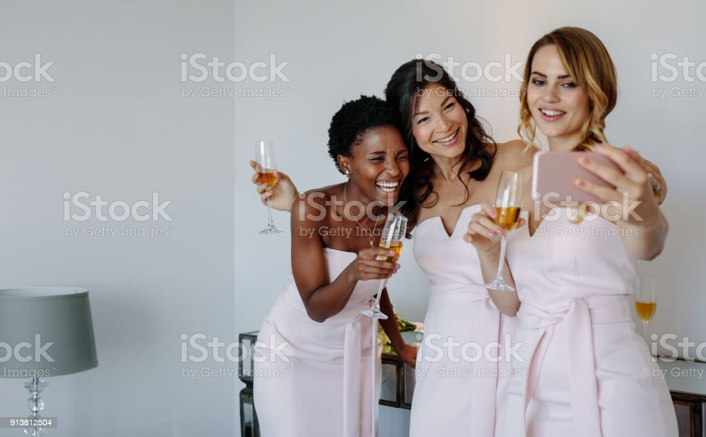 Beautiful bridesmaids taking selfie stock photo
