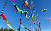 Beautiful bright kites and striped flags in the wind against the blue sky in the park