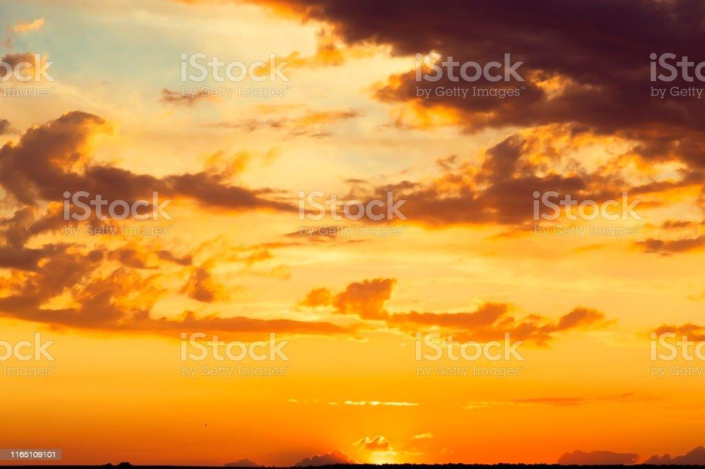 Beautiful bright majestic dramatic evening sky at sunset orange color...