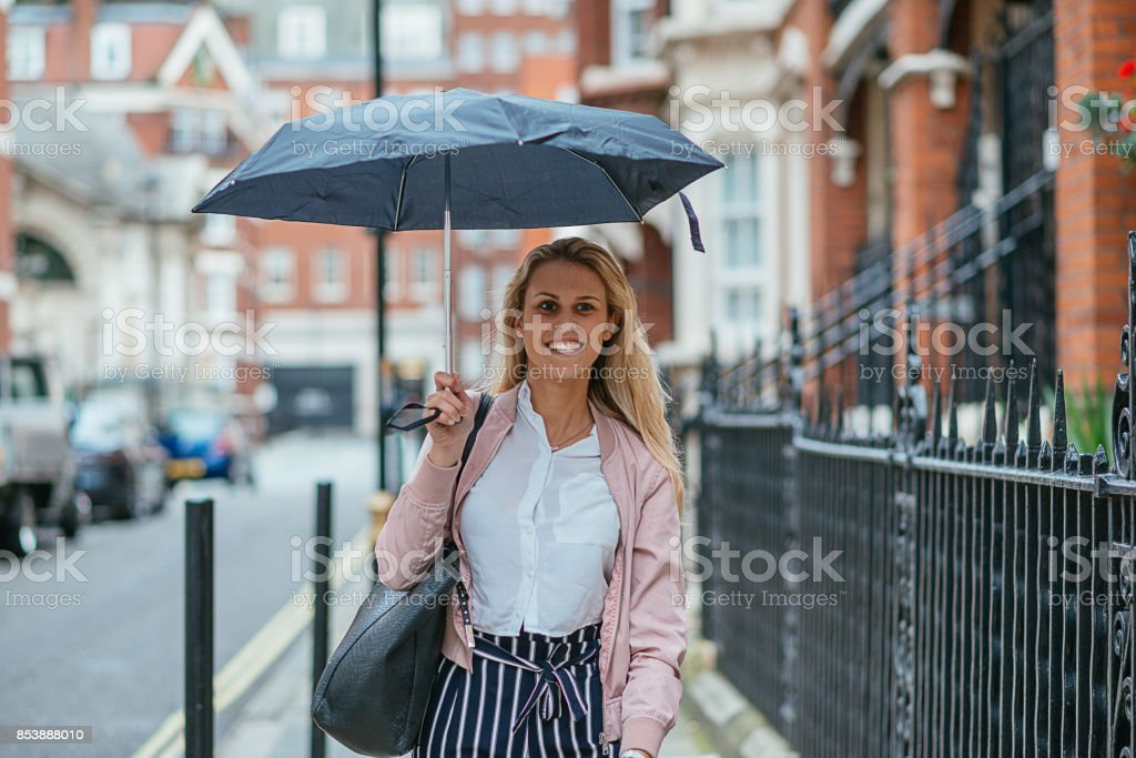 Beautiful blonde British girl with umbrella going out and walking...