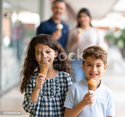 Beautiful brother and sister enjoying an ice cream while looking at camera smiling and parents standing behind - Focus on foreground