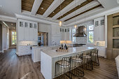 White cabinets, hardwood floor and coffered ceiling