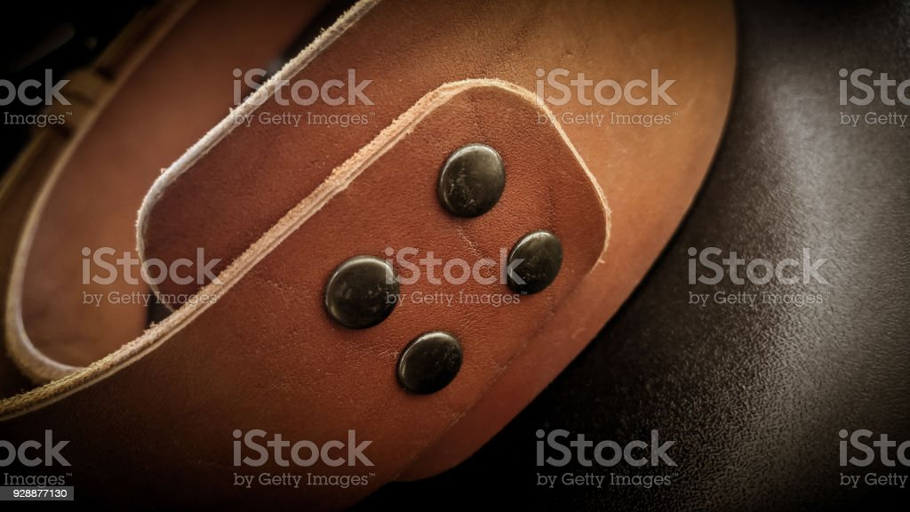 A beautiful brown hand made leather camera sling strap on a black background. stock photo