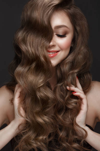 schönes braunhaariges mädchen mit perfekt gelockten haaren und klassischem make-up. schönheit gesicht und haare. - haarverlängerung stock-fotos und bilder