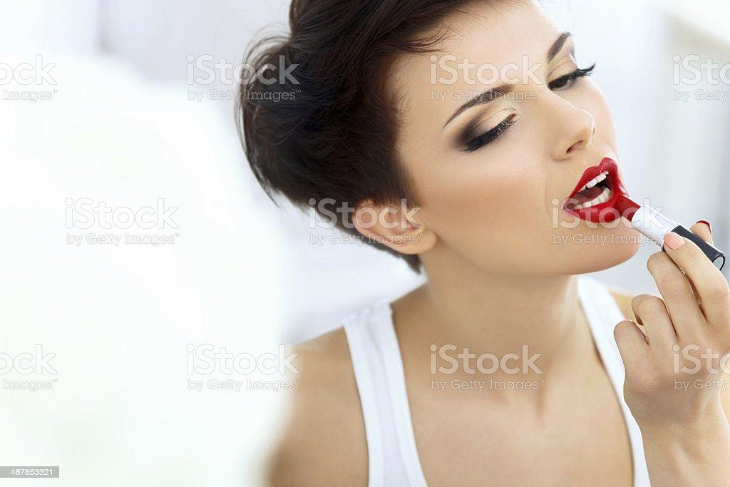 Beautiful Brunette applies lipstick.  Lipgloss and Brush. Red li stock photo