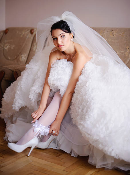 Beautiful Brunette bride getting dress her garter stock photo