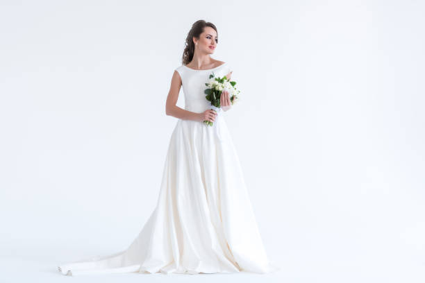beautiful brunette bride posing in white dress with wedding bouquet, isolated on white stock photo